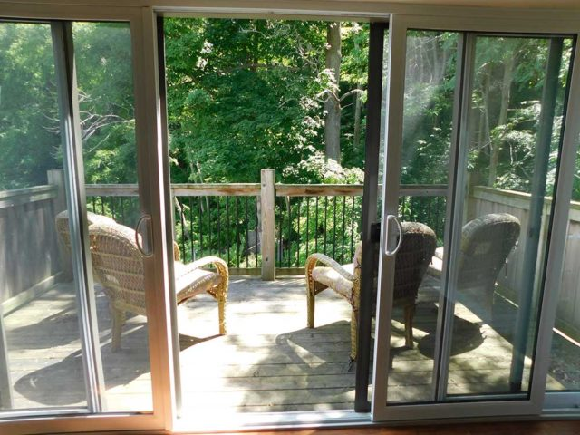 Balcony with two chairs and view of trees